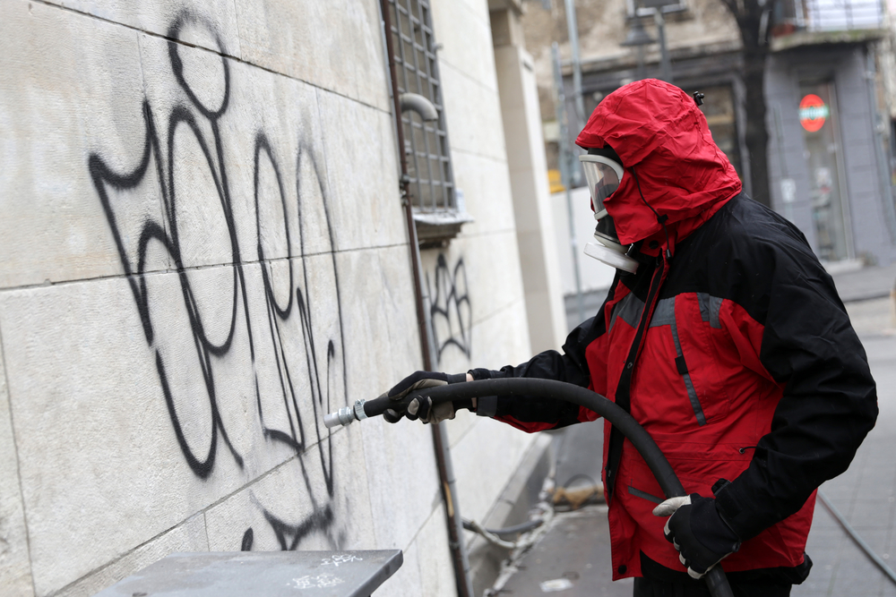 Worker cleans graffiti from a public building wall using pressure sand blaster.