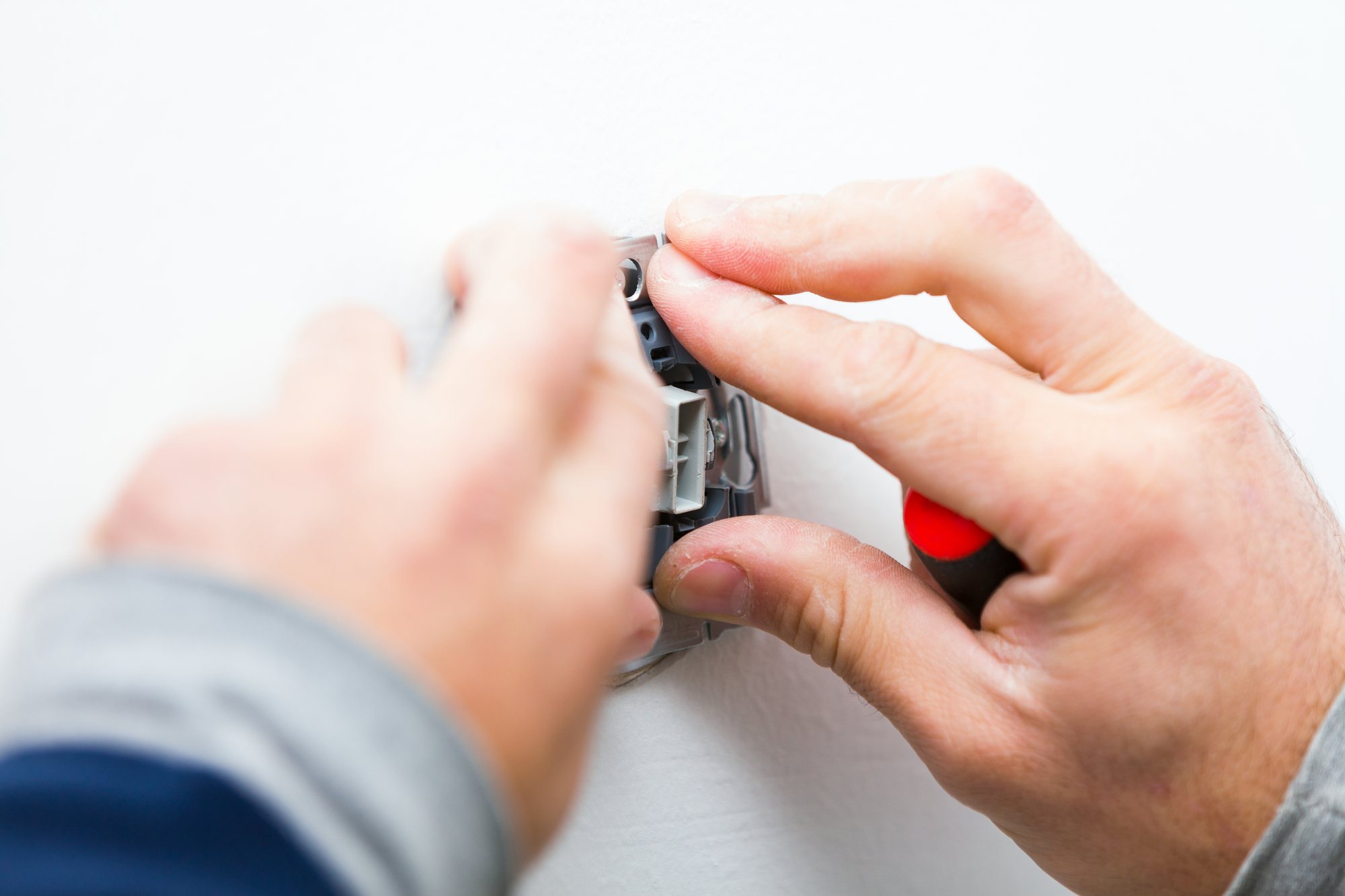 Electrician installing light on a wall using special tools.